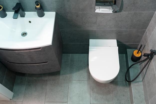 Вид сверху на компактную современную ванную комнату с туалетом и туалетным столиком, установленную на серой плиточной стене в квартире.