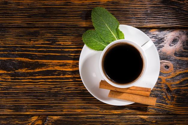 木製のテーブルの上に葉とシナモンと紅茶のトップダウンビュー