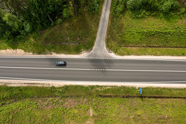 Top down view of road intersection in the forest at summer, drone shot