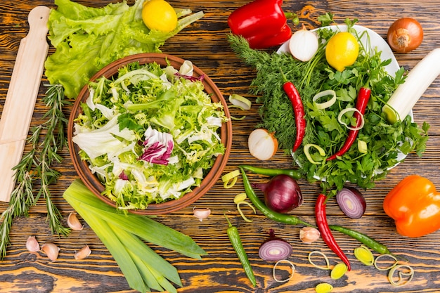 Top down view of rosemary, lettuce, leek, onion, peppers, lemon and other delicious ingredients on wooden table