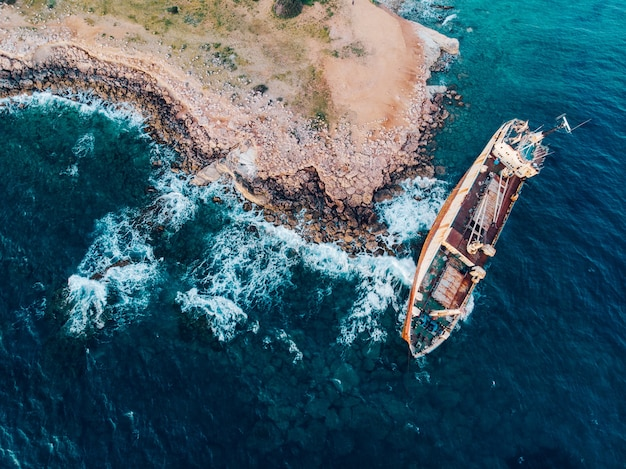 Top down view of a ship stranded near the shore, drone shot.