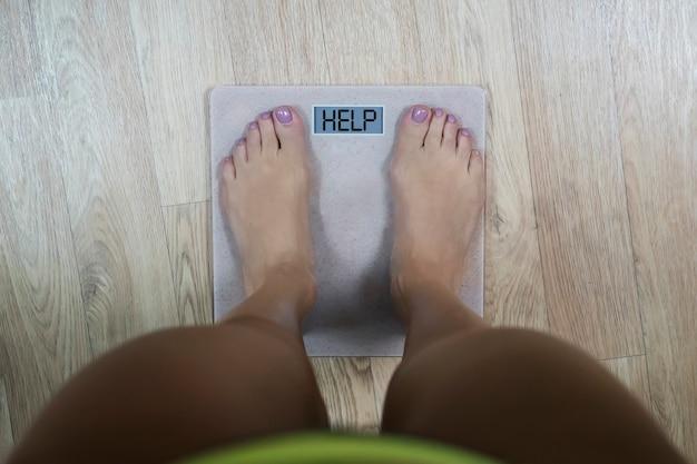 Вид сверху на женские босые ноги, стоящие на весах, с надписью help на дисплее. понятие фитнеса и похудания. женщине нужно стать стройнее. шкала, показывающая время диеты и формирования.