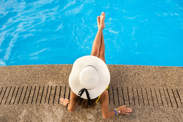 Top down view of young woman wearing yellow straw hat resting near swimming pool with clear blue water on summer sunny day.