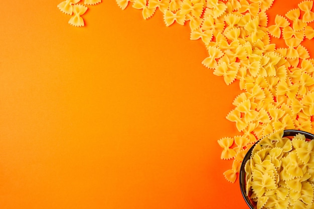 Top  dry pasta farfalle with copy space on orange