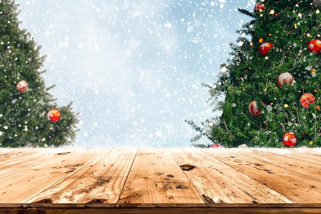 Top of empty wood table with beautiful christmas tree and snowfall background