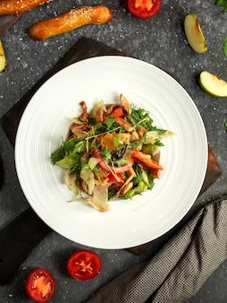 Top insalata fresca con carne di pollo pomodori erbe fresche sul piatto bianco su fondo nero