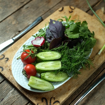 Top  fresh salad with cucumbers tomatoes and herbs on plate on wood