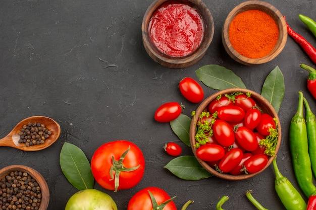 Верхняя половина вида миска с помидорами черри, острым красным и зеленым перцем и помидорами, лавровыми листьями, специями в деревянных ложках, миски с кетчупом, порошком красного перца и черным перцем на земле