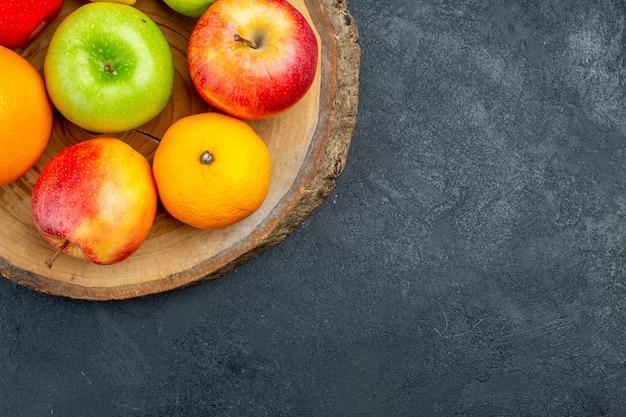 Top half view apples lemon oranges on wood board on dark surface free place