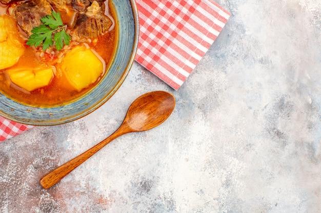 Zuppa di bozbash a metà vista dall'alto su un asciugamano con un cucchiaio di legno su sfondo nudo