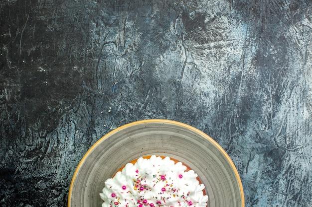 회색 테이블 여유 공간에 회색 원형 플래터에 페이스트리 크림이 있는 위쪽 절반 보기 케이크