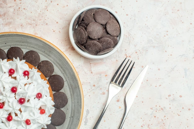 ボウルフォークとディナーナイフの楕円形プレートチョコレートにペストリークリームを添えた上半分のビューケーキ