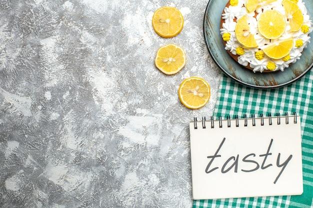 グリーンホワイトチェッカーテーブルクロスの大皿に白いクリームとレモンスライスを添えた上半分のビューケーキ。ノートに書かれたおいしい