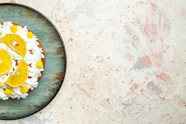 丸皿に白いペストリークリームとレモンスライスを添えた上半分のビューケーキ