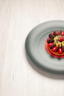 Верхняя половина вид шоколадного торта с кизилом и малиной в центре на серой тарелке с правой стороны белого деревянного стола