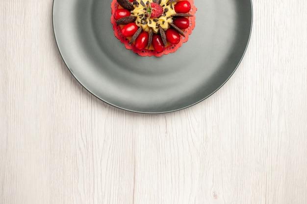 Torta al cioccolato con vista a metà superiore arrotondata con corniolo e lampone al centro nel piatto grigio su fondo di legno bianco