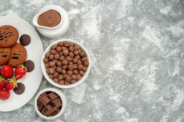 上半分のビューチョコレートクッキーイチゴと白い楕円形のプレート上の丸いチョコレートと灰色がかった白い地面にチョコレートシリアルとカカオのボウル