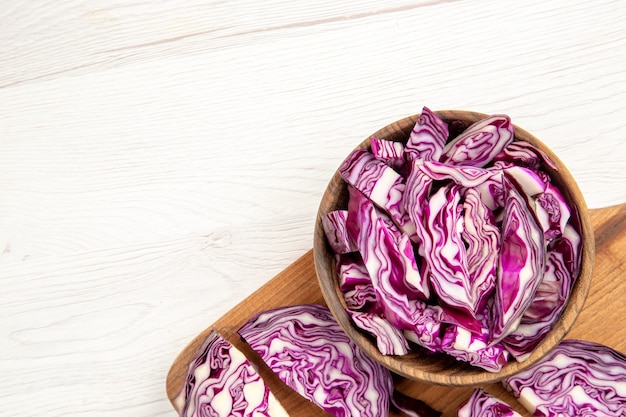 Top half view chopped red cabbages in wooden bowl on cutting board on white surface with free space