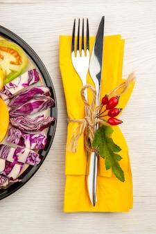 Верхняя половина вида нарезанные овощи и фрукты на черной тарелке, вилка и нож на желтой салфетке на белом столе