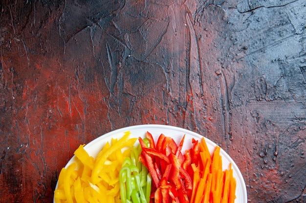 Верхняя половина вида разноцветных нарезанных перцев на белой тарелке на темно-красном столе свободное пространство