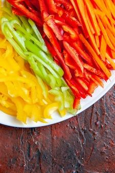 Верхняя половина вида разноцветных нарезанных перцев на белой тарелке на темно-красном столе