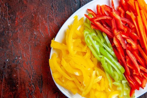 Peperoni colorati tagliati a metà vista superiore sul piatto bianco sul tavolo rosso scuro