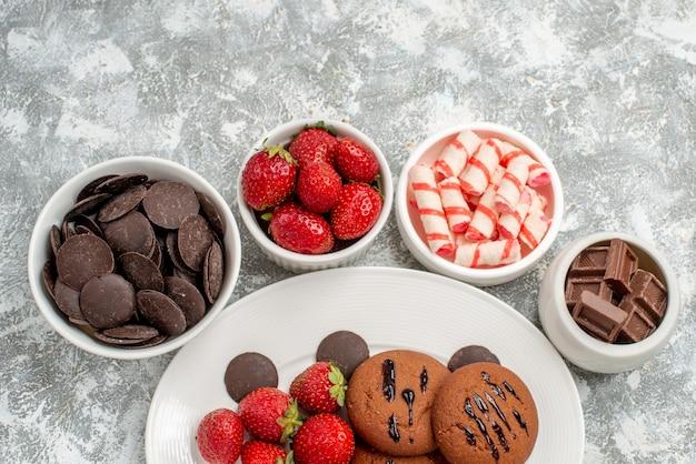 上半分のビュークッキーイチゴと白い楕円形のプレート上の丸いチョコレートは、地面にキャンディーイチゴとチョコレートでボウルを囲みました