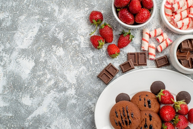 Top half view cookies strawberries and round chocolates on the white oval plate and bowls of candies strawberries chocolates on the grey-white table
