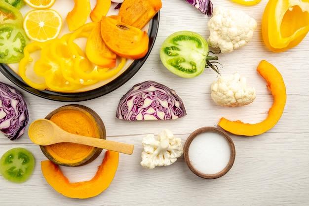 Верхняя половина вида нарезанные овощи и фрукты тыква хурма красная капуста лимон зеленые помидоры цветная капуста желтый болгарский перец на черном блюде специи в маленьких мисках на столе