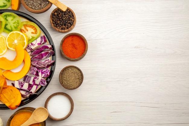 Вид сверху нарезанные овощи и фрукты, тыква, хурма, краснокочанная капуста на черной тарелке, различные специи в мисках, деревянная ложка на деревянном столе с местом для копирования