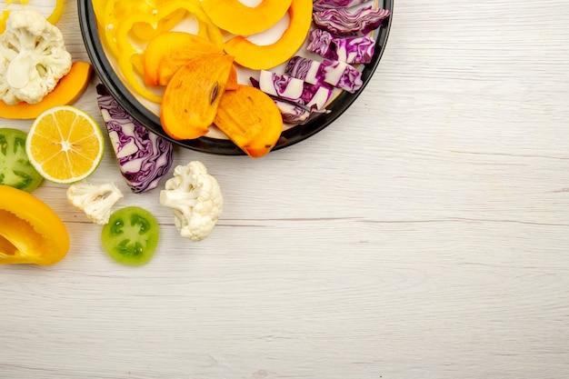 Metà superiore vista tagliare frutta e verdura zucca cachi cavolo rosso limone pomodori verdi sulla piastra nera sul tavolo con copia posto stock photo