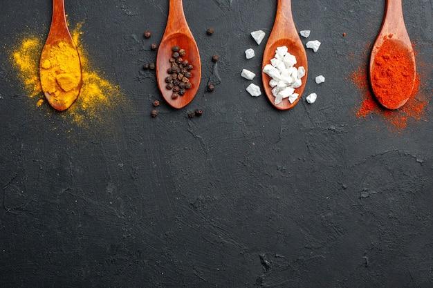 Cucchiai di legno di fila diagonale di metà superiore con curcuma pepe nero sale sae pepe rosso in polvere sulla superficie nera