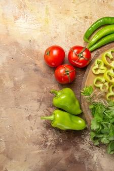 Mezza vista superiore diverse verdure tagliate a pezzi su tavola di legno di albero rotondo pomodori su sfondo giallo ocra