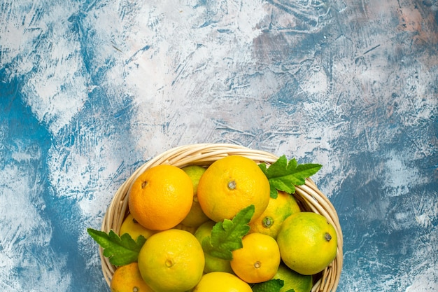 Metà superiore vista mandarini freschi su vimini crogiolarsi su spazio libero superficie bianca blu