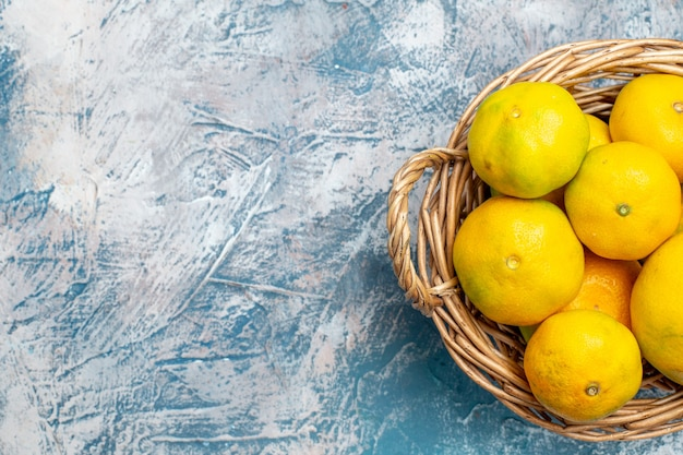 Metà superiore vista mandarini freschi sul cesto di vimini su superficie bianca blu con posto libero