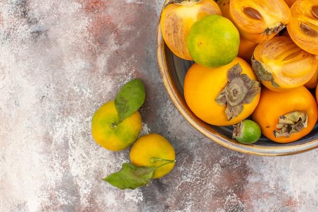 Mezza vista dall'alto feykhoas di cachi freschi in una ciotola e mandarini su sfondo nudo