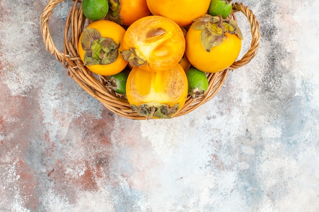 Top half view fresh persimmons in wicker basket on nude background