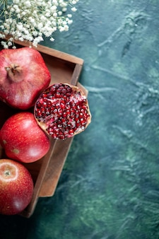 Top half view fresh pomegranates on wood serving board on table