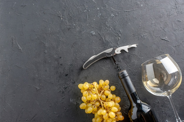 Top half view fresh yellow grapes wine opener wine glass and bottle on black table with free space