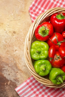 Top half view green and red peppers tomatoes in wicker basket and kitchen towel on amber background