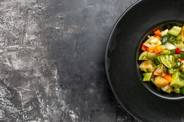 Insalata di pomodori verdi a metà vista dall'alto su piatto ovale nero su sfondo scuro