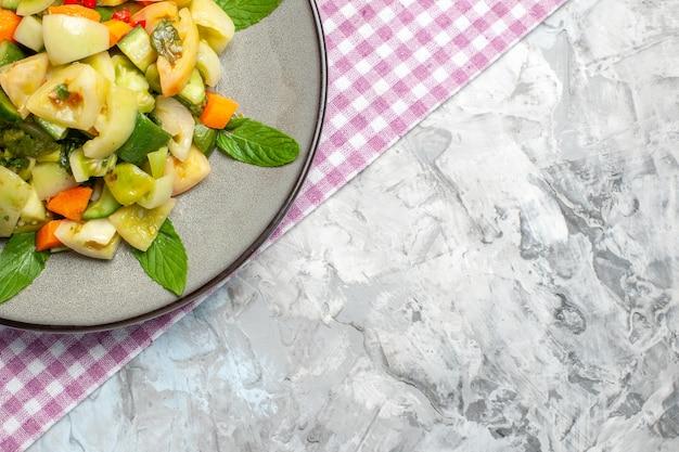 灰色の背景に楕円形のプレートピンクのテーブルクロスの上半分ビューグリーントマトサラダ
