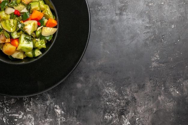 Insalata di pomodori verdi a metà vista dall'alto su piatto ovale su sfondo scuro