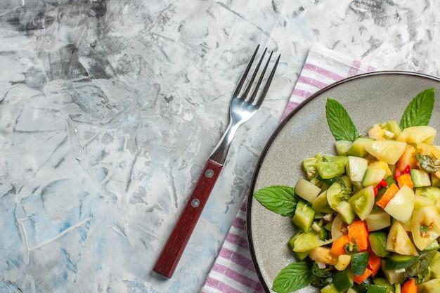 Insalata di pomodori verdi a metà vista dall'alto su piatto ovale una forchetta su sfondo scuro