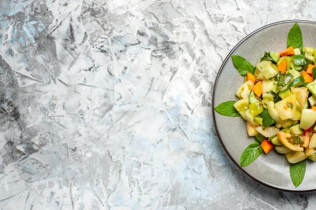 Insalata di pomodori verdi a metà vista dall'alto su piatto ovale su sfondo grigio