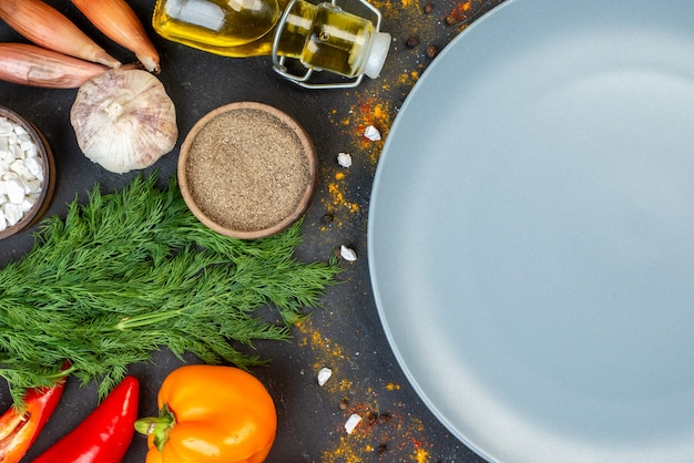 Mezza vista superiore del piatto tondo grigio verdure fresche e altri alimenti al buio