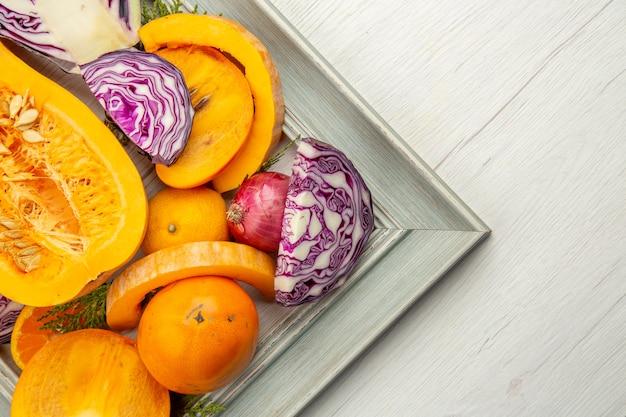 上半分ビュー半分赤キャベツバターナッツスカッシュ柿白い木製テーブルのフレームに赤玉ねぎ