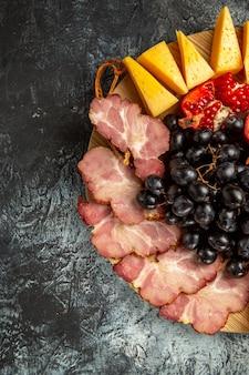 暗い背景の楕円形のサービングボード上の上半分のビューミートスライスチーズブドウとザクロ