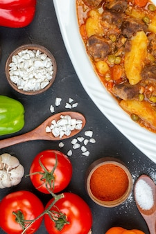 Zuppa di carne a metà vista dall'alto con sale marino guarnito in cucchiaio di legno verdure fresche su fondo nero