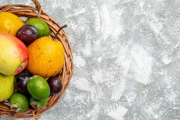 上半分のビューのプラスチック製の籐のバスケット、灰色のテーブルにリンゴ梨feykhoasプラムと柿